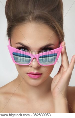 Vintage style portrait of young beautiful woman with fancy sunglasses