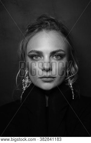 Vintage style black and white portrait of young beautiful woman with blonde hair and fancy drop earrings