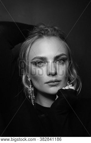 Vintage style black and white portrait of young beautiful woman with blonde hair and fancy earrings