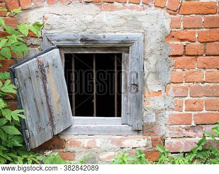 Open Cellar Window With Black Metal Bars And Wood Shutter, Old Brick House. Basement Window. Ancient