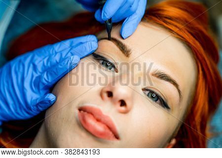 Microblading, Micropigmentation On Eyebrows In A Beauty Salon. Woman Having Her Eye Brows Tinted. Pe