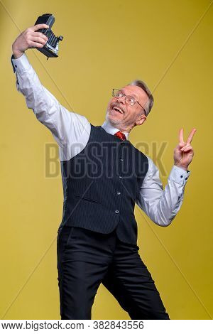 Senior Man Looking At Camera While Taking Silly Face Selfie Waving To The Camera