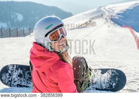Rear View Of Snowboarder In Sportswear With Equipment Resting On Top Of Ski Slope