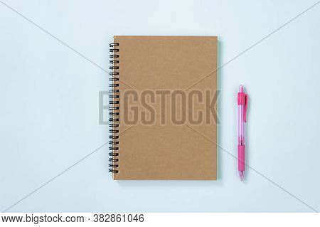 Brown Cover Spiral Notebook Or Spring Notebook In Unlined Type And Pink Pen On Blue Pastel Minimalis