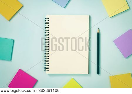 Spiral Notebook Or Spring Notebook In Unlined Type And Multi Color Sticky Note And Pencil On Blue Pa