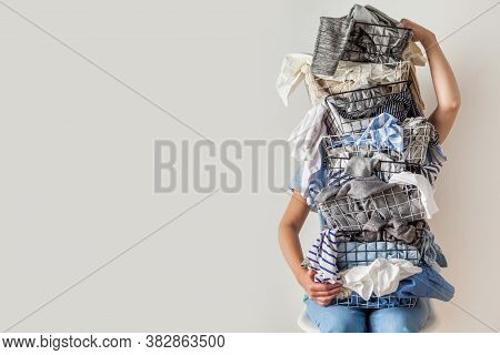 Surprised Woman Holding Metal Laundry Basket With Messy Clothes On White Background.