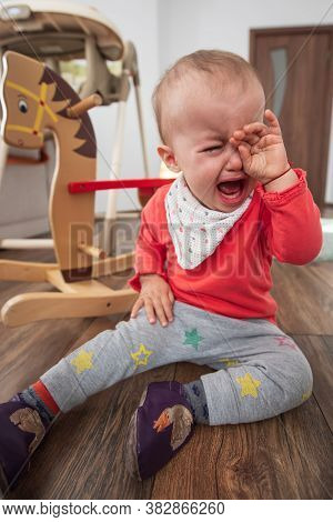 Little Girl Sitting On The Floor At Home And Crying. One Year Old Baby Crying