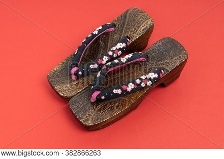 Japanese Traditional Geta Sandal On Red Background. Traditional Japanese Asian Wood Footwear Called