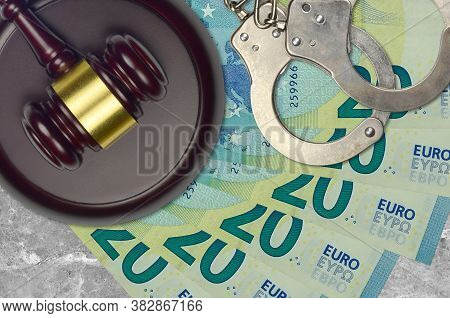 20 Euro Bills And Judge Hammer With Police Handcuffs On Court Desk. Concept Of Judicial Trial Or Bri