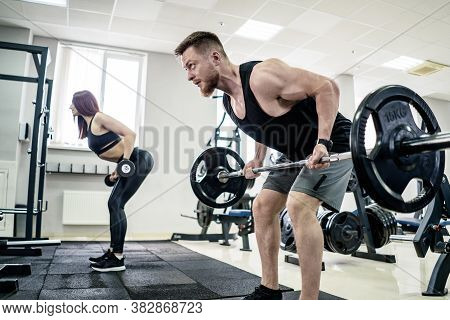 Sport, Bodybuilding, Lifestyle And People Concept - Young Man And Woman With Barbell Flexing Muscles