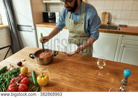 Cropped Shot Of Man Pouring Tasty Soup From Pot Into Bowl. Italian Cook Preparing A Meal In The Kitc