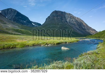 Swedish Lapland landscape. Vistasvagge valley in northern Sweden. Arctic mountain environment of Scandinavia in summer day and clear water of Visstasjohka river