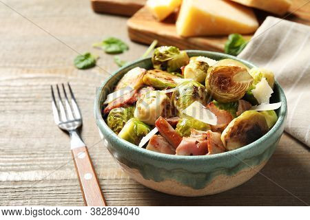 Delicious Fried Brussels Sprouts With Bacon In Bowl On Wooden Table