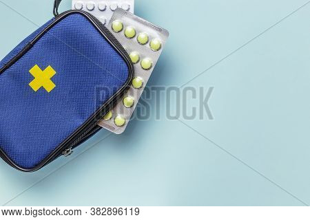 First Aid Kit With A Cross On A Blue Background With Copy Space, Medicines, Pain Relievers Pills, An