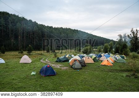 Tent Camp On The River Bank, Colorful Tents Stand In The Field, Morning In A Tourist Camp, Cloudy We