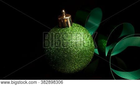 Green Ribbon And Christmas Ornament Glistening On A Black Background