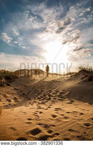 Lonely Man Walking In The Desert Dunes At Sunset.
