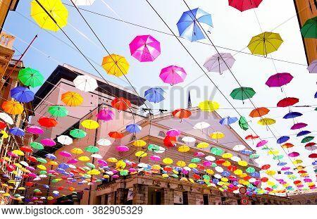 Genova, Italy - 0/29/2020: Multicolored Umbrellas Against The Sky, Street Decorated. Lgbt Flag. Rain
