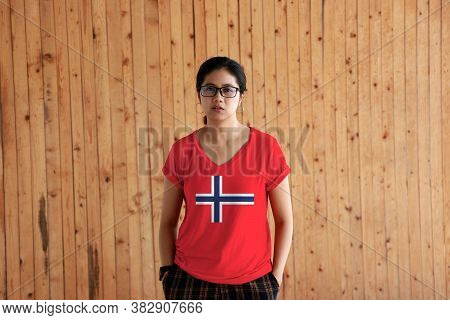 Woman Wearing Norway Flag Color Shirt And Standing With Two Hands In Pant Pockets On The Wooden Wall