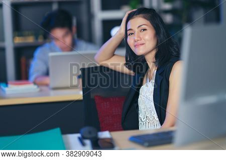 Businesspeople In The Office At Night Working Late, Two Young Businesspeople Working Overtime Togeth