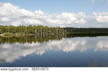 Forest Lake View, Smooth Surface Of A Lake With Clouds Reflected, Shining Level Of A Forest Lake