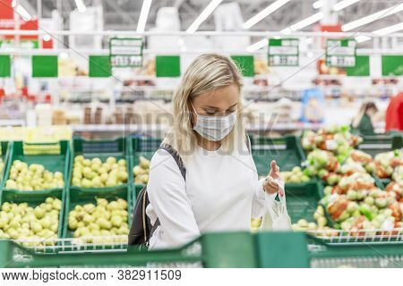 Young Blonde Woman In A Medical Mask Chooses Fruits In A Large Hypermarket. Health And Proper Nutrit