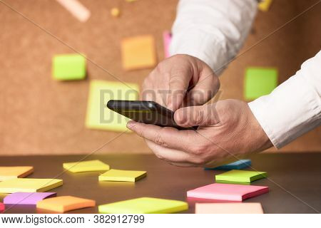 Businessman Using A Smartphone And Post In A Brainstorming Session. Business Brainstorming Concept