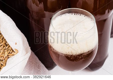 Glass Of Home Made Craft Beer And A Bag Of Light Malt On A Wooden Table On White Background. Craft B