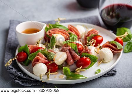 Appetizer Antipasto Skewers With Tomatoes, Salami, Mozzarella And Basil