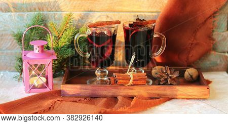 Merry Christmas, Cups With Mulled Wine, Spices On A Wooden Tray, Fir Branches, A Lantern With A Cand