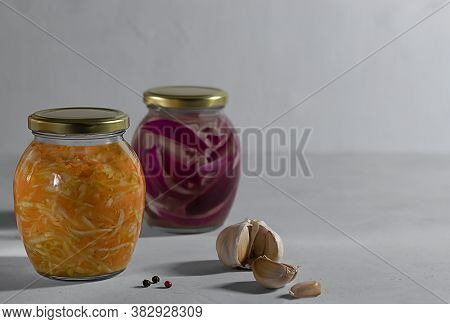Two Small Glass Jars Of Fermented Vegetables, A Jar Of Sauerkraut In Focus, And A Jar Of Purple Onio