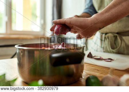 Close Up Of Hands Of Man, Chef Cook Adding Onion To The Pot With Chopped Vegetables While Preparing