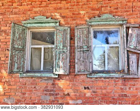 Dilapidated House With Wooden Shutters. Open Wooden Shutters With Peeled Paint. Old Vintage Window