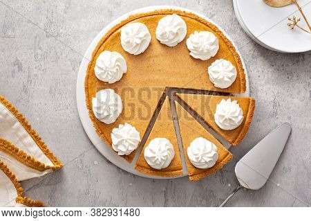 Pumpkin Pie With Whipped Cream With Slices Taken Out