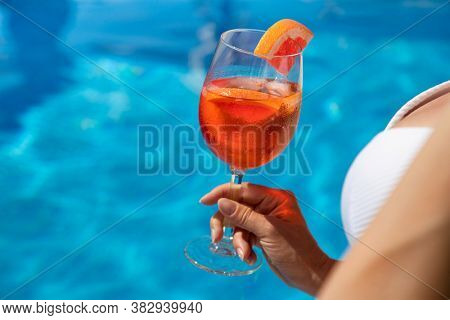beautiful woman with cocktail sitting on the edge of the swimming pool, relaxation concept