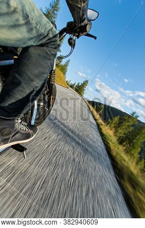 Motorcycle rider driving in Alps, beautiful nature with clear sky. Travel and freedom, outdoor activities. Low angle