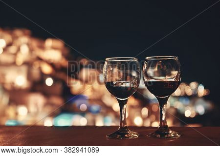 Leisure life settings at night with wine and bokeh in Santorini, Greece.