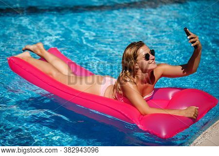 Sexy Woman With A Phone In A Swimsuit Lies On A Pink Inflatable Mattress In The Pool. Relax By The P