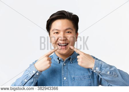 Orthodontics And Stomatology Concept. Close-up Of Happy Smiling Asian Man Pointing Fingers At Dental