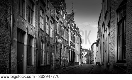 Brugge / Belgium - Sept. 18, 2018: Black And White Photo Of A Typical Cobblestone Street With Brick