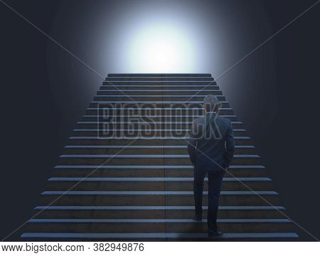 Back View Of Business Man In The Dark Walking Climbing Stairs Exit To Top With Bright Light. Creativ