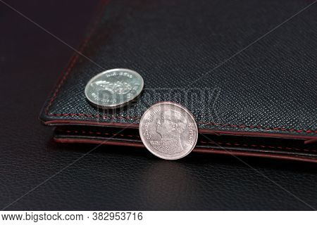 Thai One Baht Coins On Obverse (thb) And Out Focus One Baht Coins On Reverse With Black Wallet, The