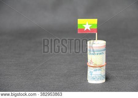 Rolled Banknote Money Ten Thousand Myanmar Kyats And Stick With Mini Myanmar Flag On Dark Grey Floor