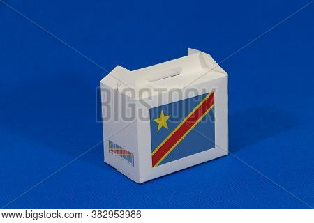 Dr Congo Flag On White Box With Barcode And The Color Of Nation Flag On Blue Background. The Concept