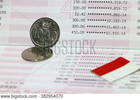 Two Coins Of One Thousand Rupiah With Mini Indonesia Flag On The Book Bank. Concept Of Saving Money