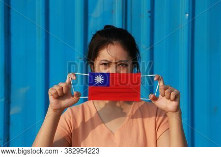A Woman With Taiwan Flag On Hygienic Mask In Her Hand And Lifted Up The Front Face On Blue Backgroun