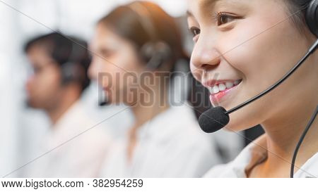 Smiling Asian Businesswoman Consultant Wearing Microphone Headset Of Customer Support Phone Operator