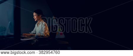 Smiling Asian Business Woman Sitting The Table And Working On Computer In Office At Night. Take Your