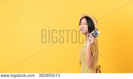 Young Smiling Asian Woman Tourist Holding Camera And Looking To Copy Space On Yellow Background.