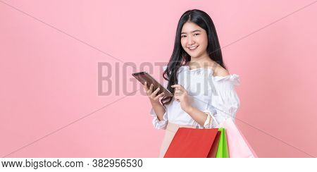 Cheerful Beautiful Asian Woman Holding Multi Coloured Shopping Bags And Digital Tablet On Light Pink